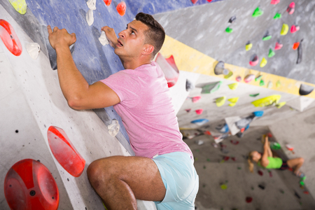 Sporty man training at bouldering gym without special climbing equipment