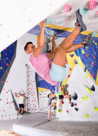 Cheerful  male alpinist practicing indoor rock-climbing on artificial boulder without safety belts Banco de Imagens - 106758223