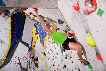 Smiling positive sporty woman training at bouldering gym without special climbing equipment Banco de Imagens