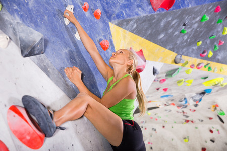 Young glad cheerful  sporty woman training at bouldering gym without special climbing equipment