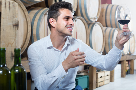 positive adult professional man having wine tasting in cellar with woods