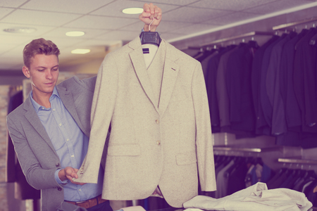 Portrait of man offering business style jacket in the shop Banco de Imagens - 106767671