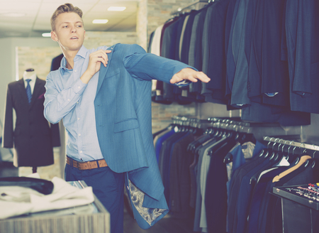 Portrait of man costumer trying business style jacket in the shop