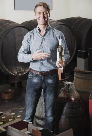 smiling man customer picking bottle of wine in wine cellar