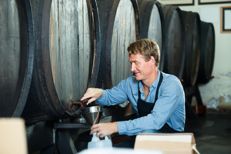 professional man working in winery wearing apron pouring wine from wood to plastic bottle in cellar
