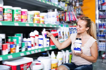 smiling young woman customer choosing paint medium in bottle in housewares hypermarket Foto de archivo