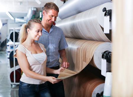 smiling man and woman customers choosing bolt of linoleum in household section Stock Photo