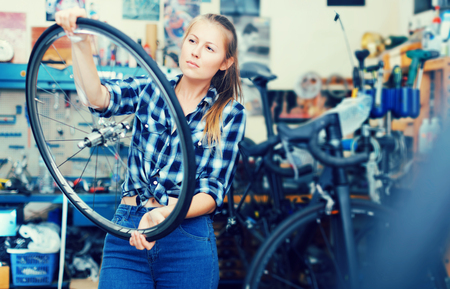 young woman worker is standing near bicycle for replacing wheels in workshop.
