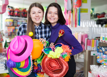 Portrait of happy comically dressed girls joking in festive accessories shop