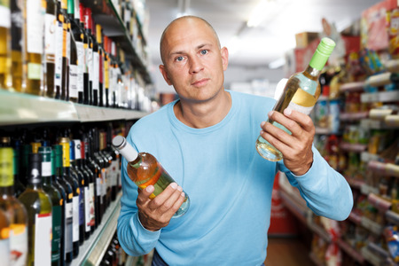 Portrait of concentrated man customer looking bottle of white wine in supermarket