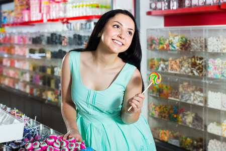 smiling sexy girl posing in the store with lolly on the background of counters with sweets