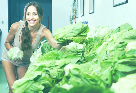 cheerful smiling young woman customer buying fresh green iceberg salad in store Zdjęcie Seryjne
