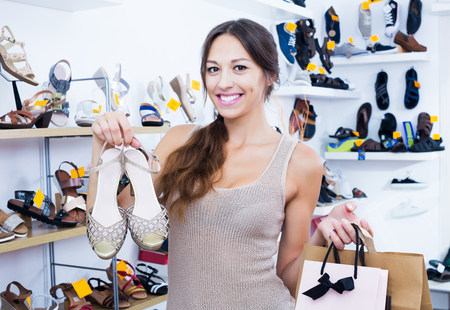 Happy brunette woman standing in boutique with shopping bags and chosen shoes in boutique