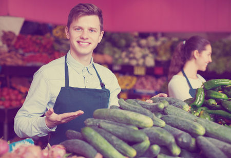Two friendly young market stuff offering for retail slicing cucumbers