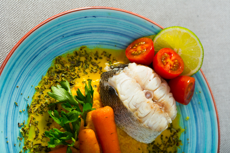 Recipe of steamed merluccius with vegetable pate: carrots, onion, garlic fry in dry frying pan, beat in blender with olive oil and salt. 250g of fish steam for 15min. Serve with fresh herbs and lemon