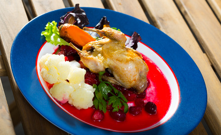 Fried tasty quail with caramelized carrots, cranberry sauce, greens and vegetables