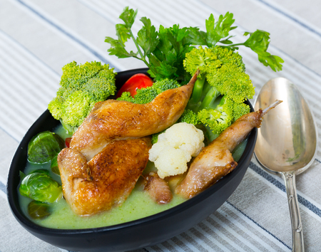 Vegetable broth with cauliflower, Brussels sprouts and broccoli served with fried quail meat, tomatoes and parsley