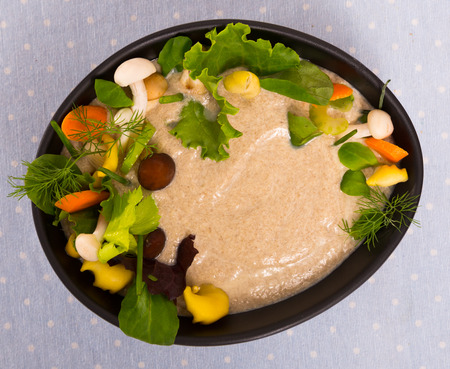 Top view of creamy soup with shiitake, oyster mushrooms, honey agarics and champignons served in black bowl with greens and vegetables 版權商用圖片