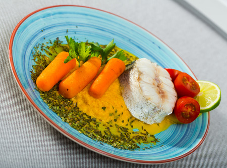 Steamed merluccius served with vegetable pate. Recipe: carrots, onion and garlic bake and beat in blender, add olive oil and salt. Fish steak 250g steam for 15 minutes. Serve with pate, greens, lemon