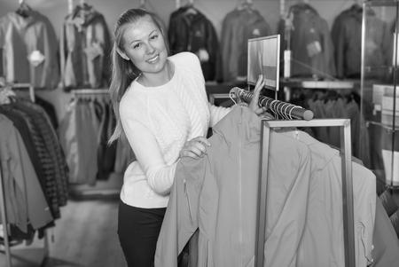 Joven esbelta en tienda de deportes elige su ropa y zapatos para entrenamiento