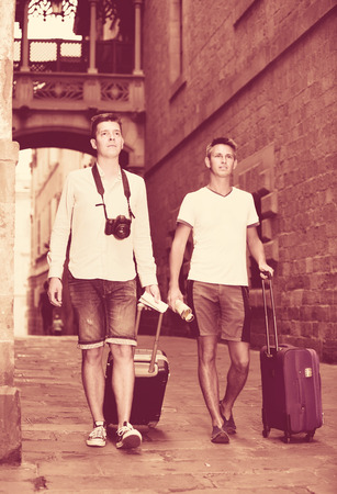 positive spanish male couples with travel bags walking the city