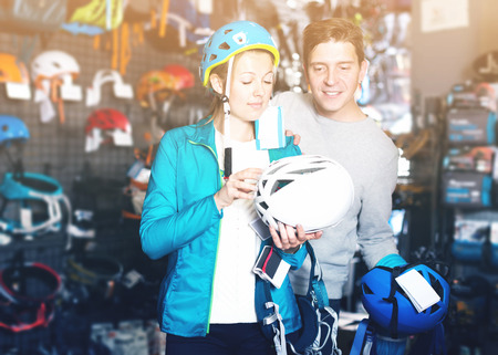 Young couple in sports store choosing helmet and other sports equipment