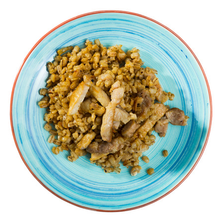 plate with barley porridge with pork roast. Isolated over white background