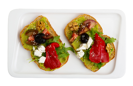 Delicious sandwiches with guacamole, fresh tomatoes, sweet pepper and feta cheese. Isolated over white background 版權商用圖片