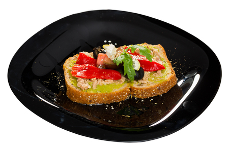 Healthy sandwich with guacamole, canned tuna, feta cheese, fresh vegetables and lemon served on black plate. Isolated over white background Zdjęcie Seryjne