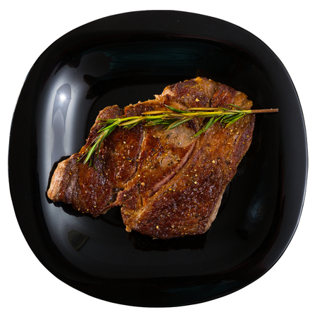 Top view of grilled veal steak with rosemary served on black plate. Isolated over white background Stock Photo