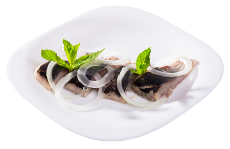 Slices of pickled herring with onions decorated mint leaves served on white plate. Isolated over white background