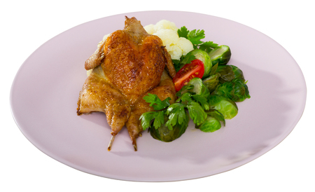 Whole fried quail served with steamed cauliflower and brussel sprouts. Isolated over white background
