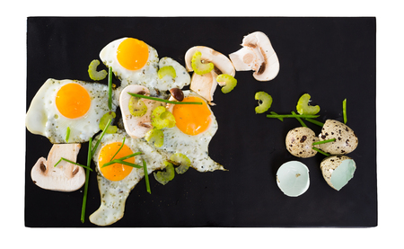 Fried quail eggs with mushrooms, chives and celery. Isolated over white background