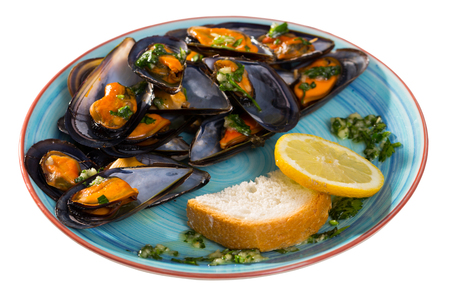 Baked mussels on plate served with parsley, toast and lemon. Isolated over white background