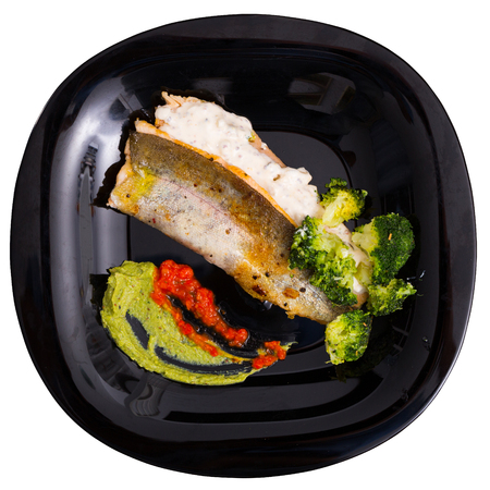 Delicious fried brook trout fillets with broccoli and tartare saucee. Isolated over white background