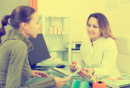 Young female client visiting for consultation in a aesthetic medicine center. Focus on doctor