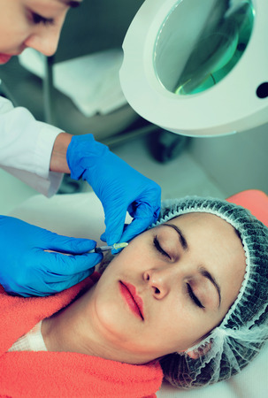 Glad  positive female doctor doing beauty injection to young woman client