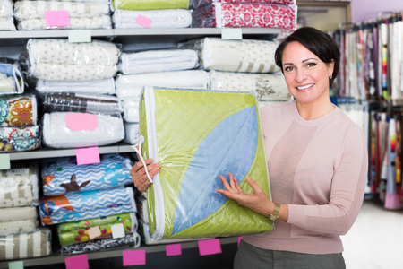 Happy female customer handles bedspread near textiles shelves inside
