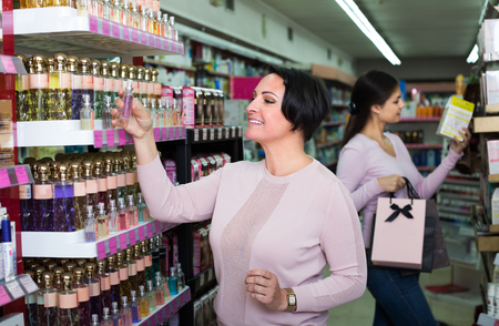 Cheerful young girl and happy mature woman choosing perfume in beauty department Foto de archivo