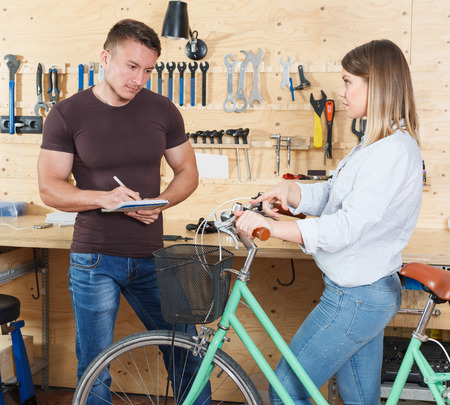 young girl consults about repairing a bicycle with a male master in the workshop. Stock fotó