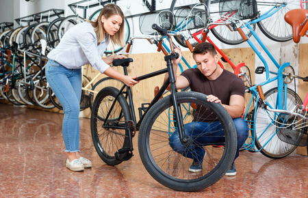Happy positive smiling couple is choosing modern bicycle in the bike store. Stock fotó