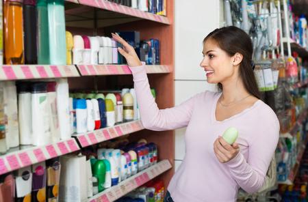 Vrolijk Amerikaans jong meisje die deodorant in schoonheidsafdeling kiezen Stockfoto