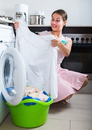Portrait of smiling housewife satisfied with quality of washing in kitchen