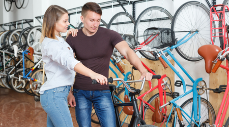 Smiling pair is choosing modern bicycle together in the bike store.