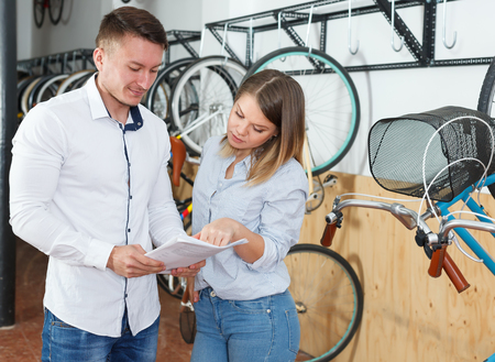 Smiling couple is choosing modern bicycle with bike characteristic in the bike store