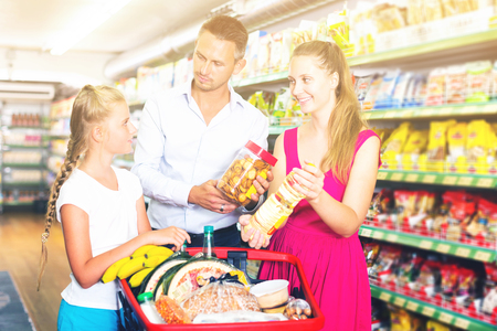 portrait of happy family of three smiling and standing with purchases in shopping mall Reklamní fotografie