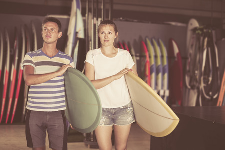 Young couple is ready for surfing with surfboard in summer