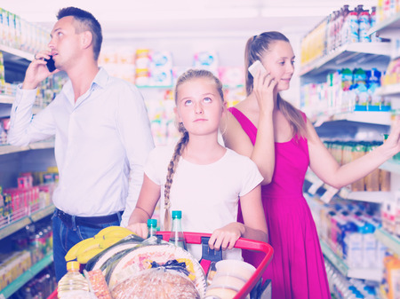 frustration kid and young parents with phones in food supermarket Standard-Bild
