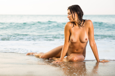 Absolutely naked young woman sitting on beach against azure sea