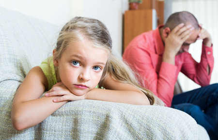 Portrait of little daughter quarrelling with father at home Stock Photo